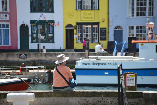 Jacqui watching the boats go past in Weymouth Harbour.